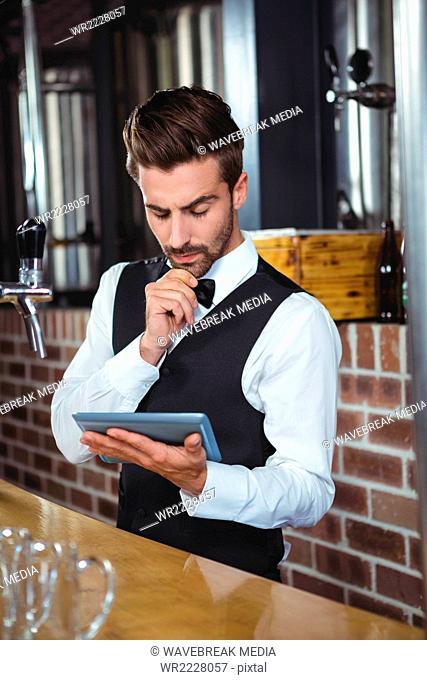 Handsome barman using tablet computer