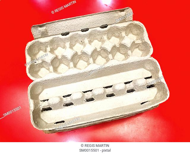 Empty eggs carton on a red background