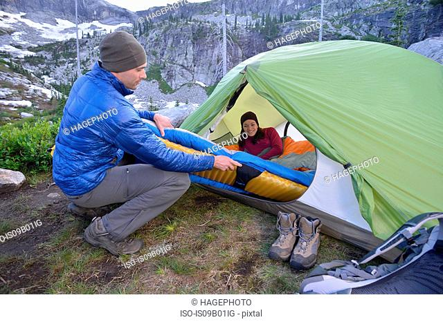 Couple putting sleeping bag in tent at dusk, Fault Lake, Selkirk Mountains, Idaho