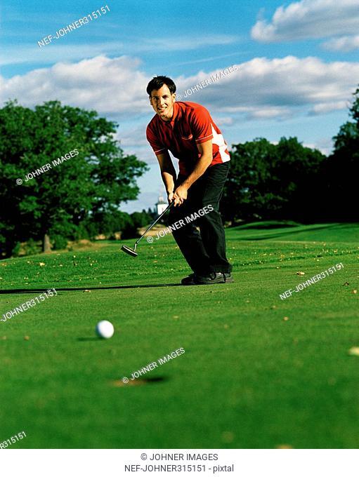 Male Scandinavian golfer putting, Sweden