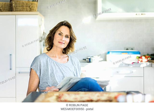 Portrait of woman with newspaper in kitchen at home