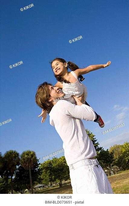 Hispanic father lifting daughter into the air