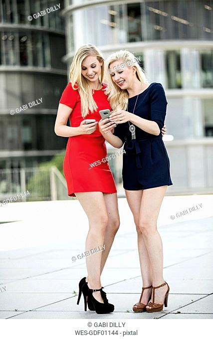 Two fashionable women looking at their smartphones