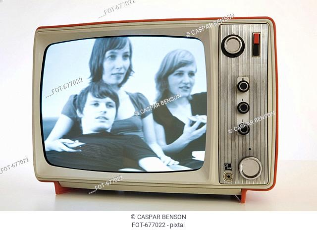 A televison with a black and white image of three young people
