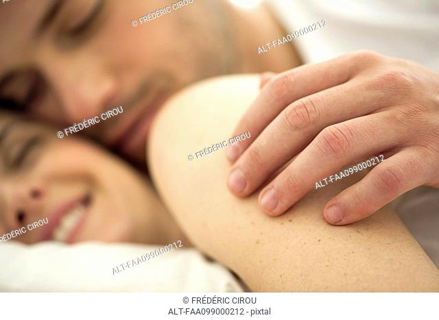 Couple cuddling together in bed, husband's hand on wife's shoulder, close-up