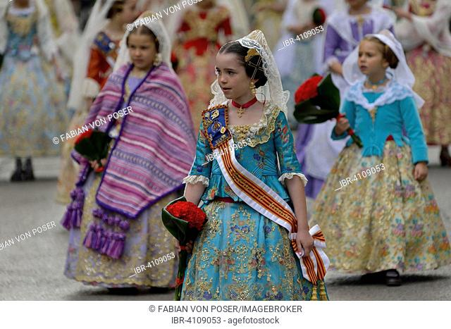 Fallas festival, girls in a traditional costume during the parade in the Plaza de la Virgen de los Desamparados, Valencia, Spain