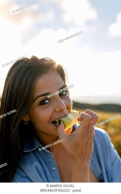 Spain, Asturias, beautiful young woman eating an apple