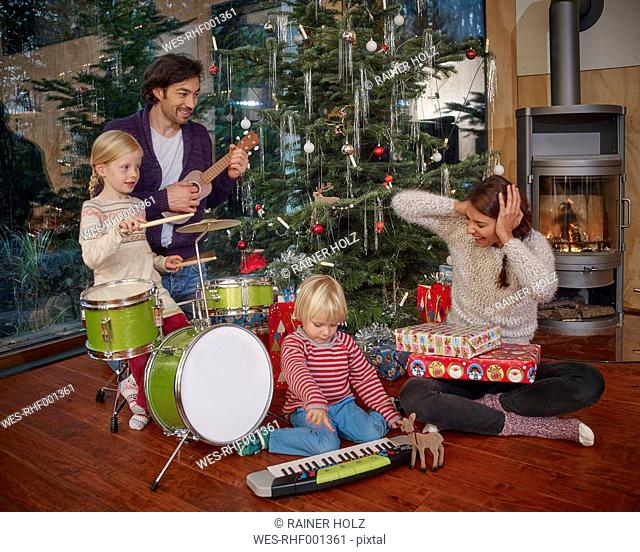 Father and daughters playing music on Christmas Eve