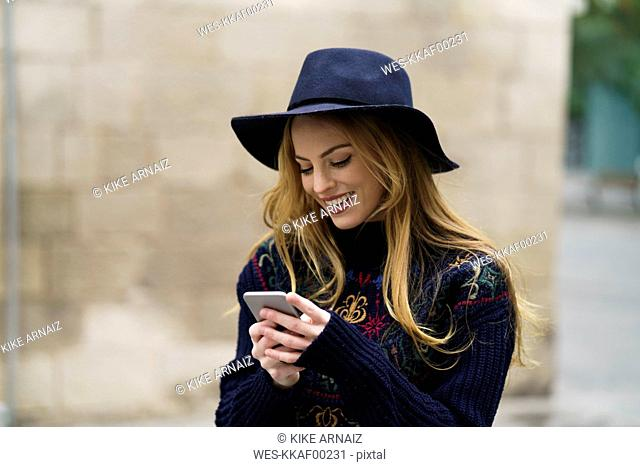 Smiling young woman looking at cell phone