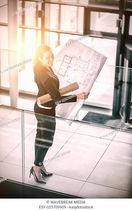 Businesswoman standing at office corridor with blueprint