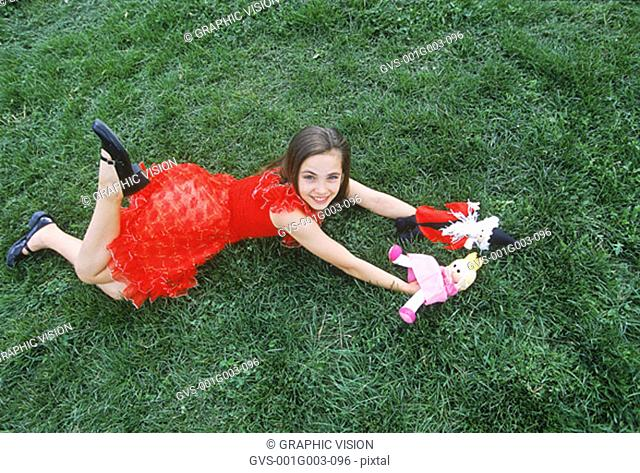 Young girl lying on grass with her dolls looking up