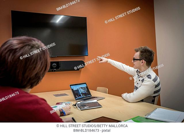 Caucasian students using television in study room