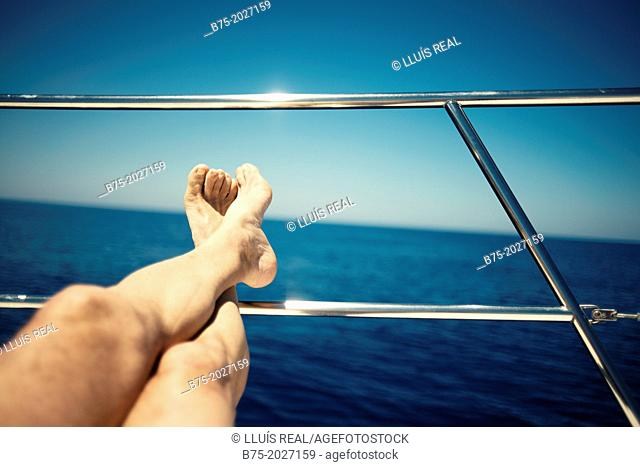 man legs resting on a railing of a sailing boat in a relaxed posture