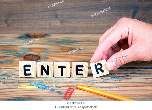 Enter. Wooden letters on the office desk. Business and communication background