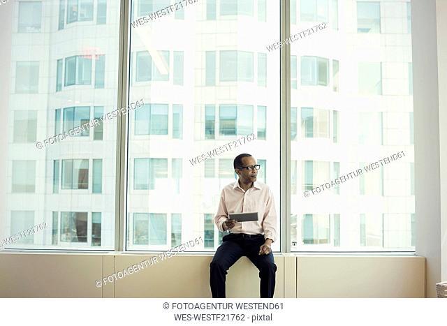 Businessman sitting on window sill holding digital tablet