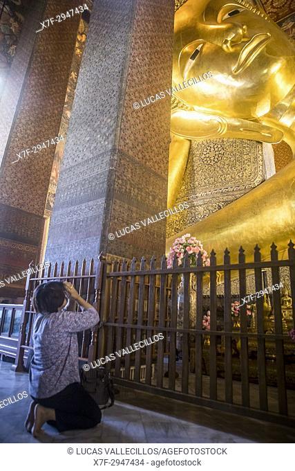 Woman praying, Golden big Buddha, in Wat Pho or Wat Phra Nakhon temple in Bangkok, Thailand
