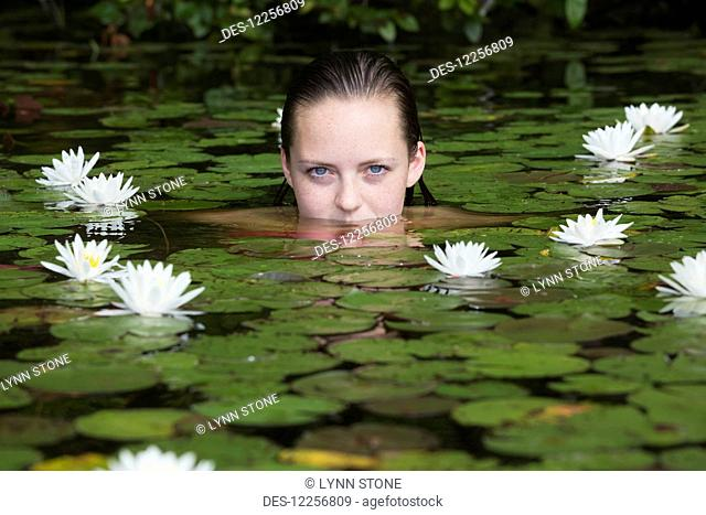 Young woman in water among the water lilies; Connecticut, United States of America
