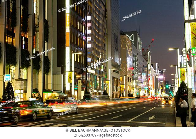 Tokyo Japan local crowds Ginza shopping twilight traffic blurs of movement on street downtown with rush of locals and tourists shop and drive along famous...