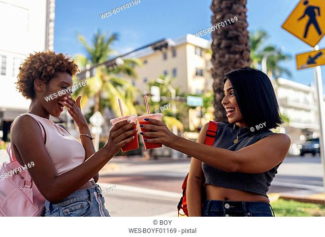 USA, Florida, Miami Beach, two happy female friends having a soft drink in the city