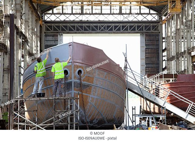 Two workers painting boat in shipyard