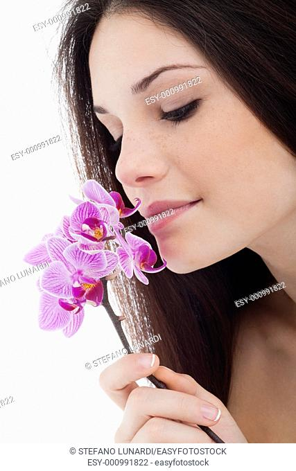 Beautiful young woman smelling flower
