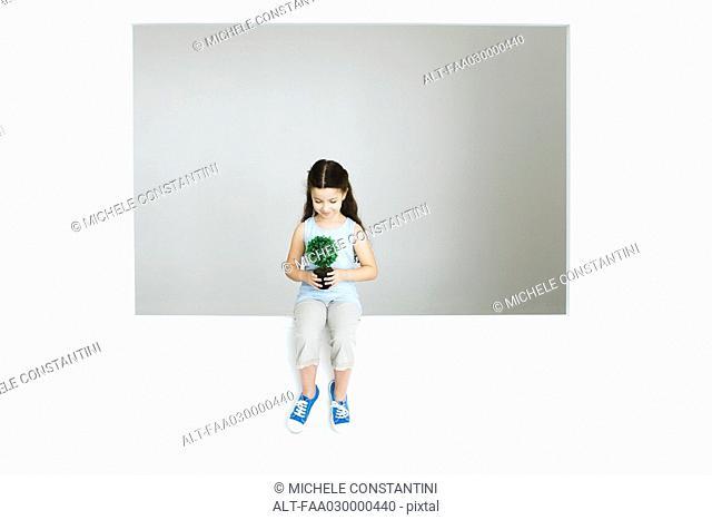 Little girl holding plant, full length