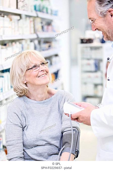 Pharmacist checking blood pressure