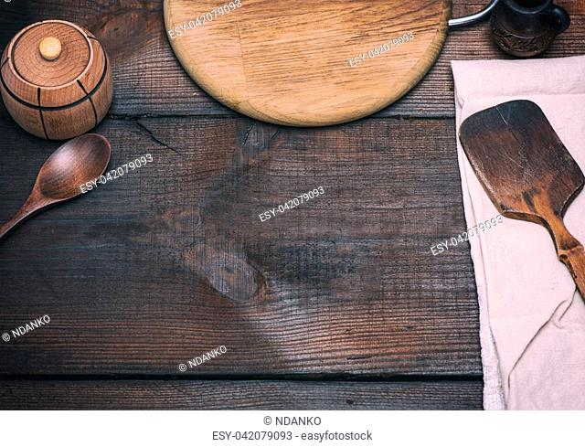 wooden kitchen spatula and round cutting board on a brown background, empty space in the middle