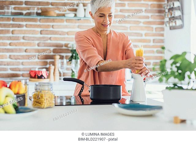 Older Caucasian woman cooking spaghetti in kitchen