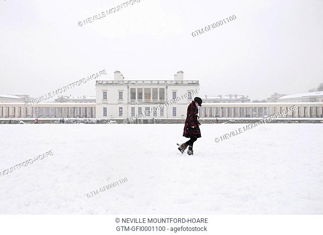 Woman walking in snowy landscape in Greenwich park with Queen's House behind