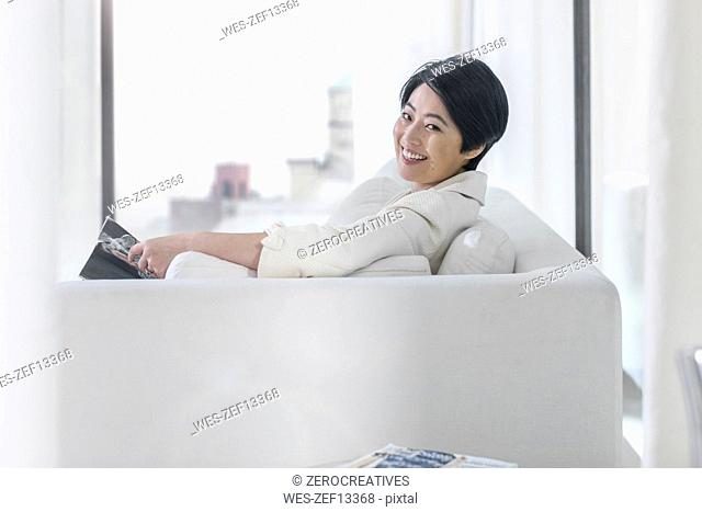 Portrait of smiling young woman on couch with book