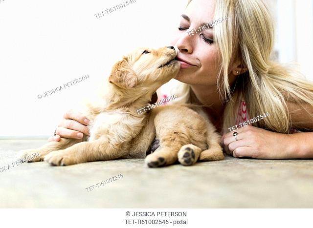 Owner kissing Golden Retriever puppy