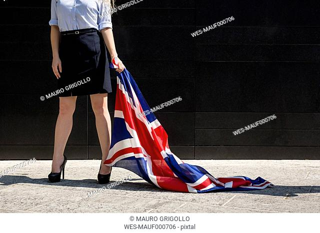 Businesswoman standing outdoors holding British Flag