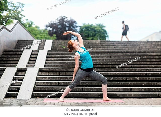 Young woman doing yoga on staircases in urban city, Freiburg im Breisgau, Baden-Württemberg, Germany
