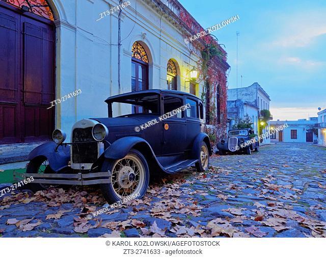 Uruguay, Colonia Department, Colonia del Sacramento, Vintage cars on the cobblestone lane of the historic quarter