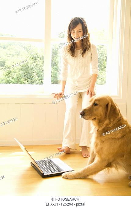 Woman with her dog who is sitting in front of a laptop