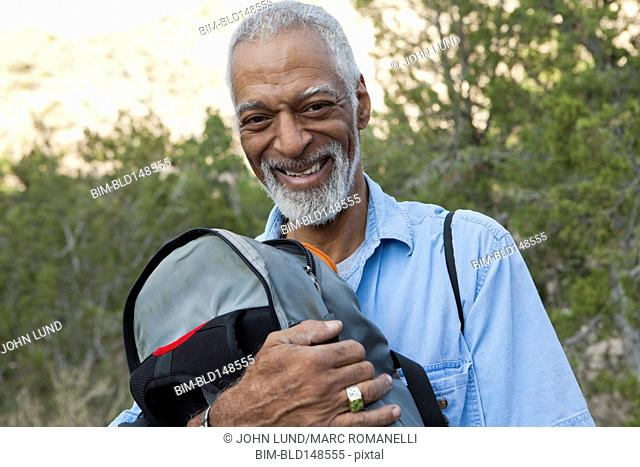 African American hiker holding backpack