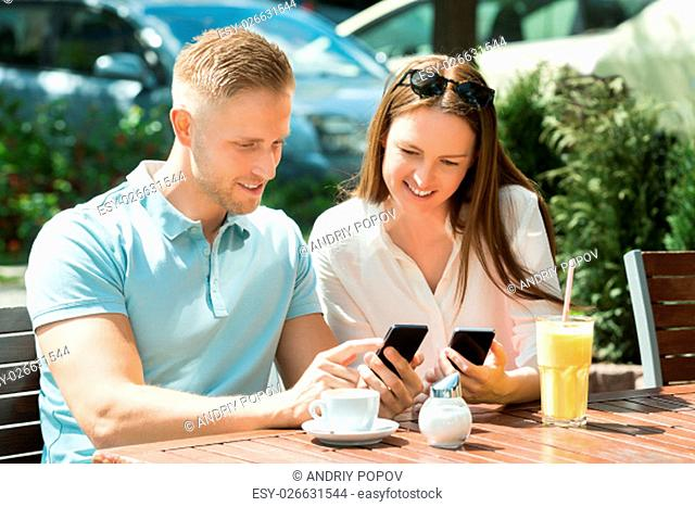 Young Happy Couple Sitting On Bench Using Mobile Phone
