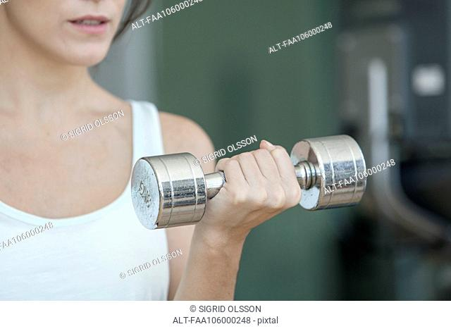 Woman lifting dumbbell, cropped