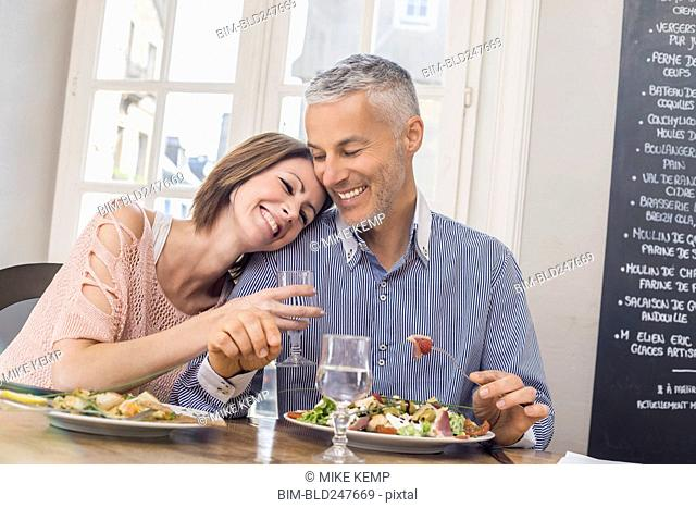 Caucasian couple cuddling in restaurant