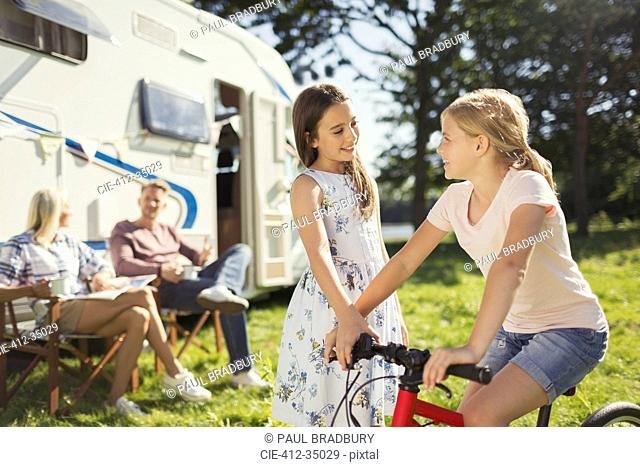 Sisters with bicycle outside sunny motor home