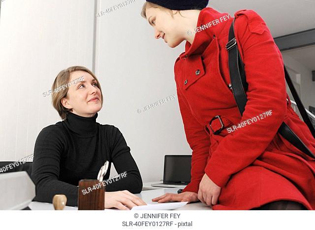 Businesswomen talking at desk in office