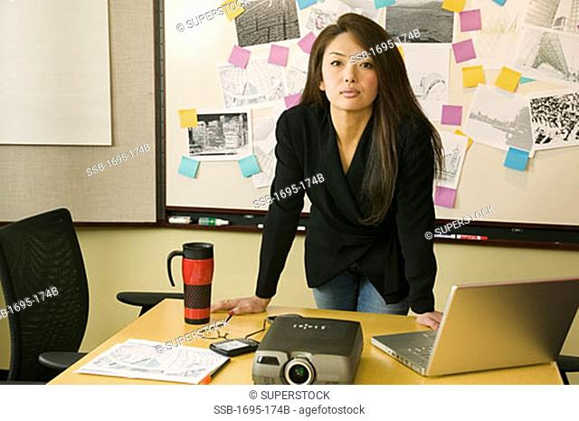 Front view of a businesswoman leaning on a table in a conference room