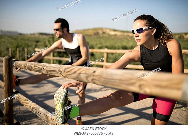 Sportive man and woman stretching on a bridge