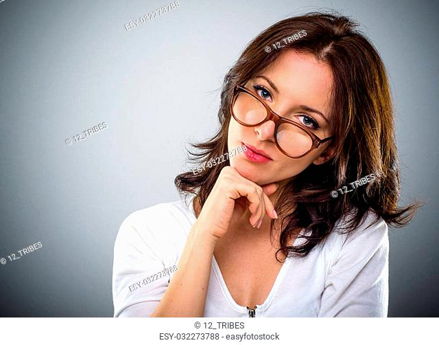 193f4c06ee Thoughtful attractive young brunette woman wearing glasses resting her chin  on her hands peering over the