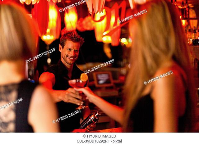 Bartender handing woman a cocktail
