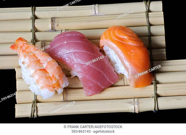 Pieces of shrimp, tuna and salmon sushi on a plate made of bamboo tied together making a serving tray