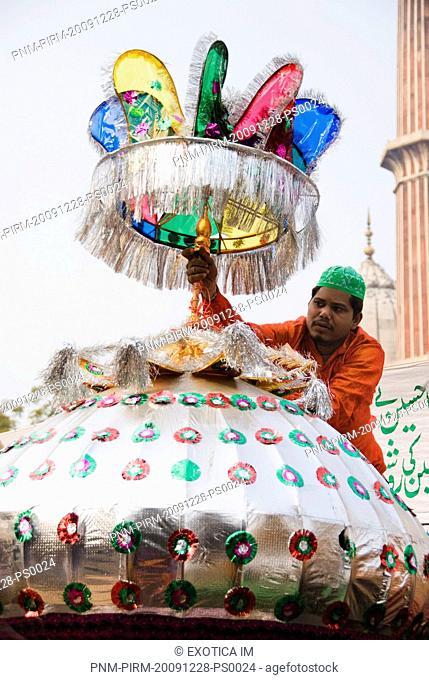 Man decorating Tazia at a mosque during Muharram, Jama Masjid, Delhi, India