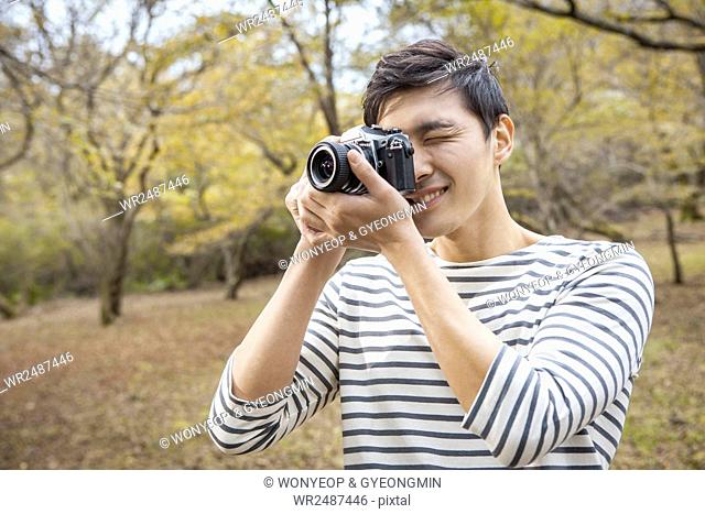 Portrait of young man holding a camera and taking a picture in park