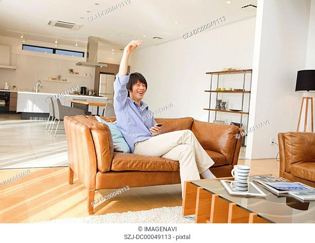 Middle-aged man using a smartphone on a sofa